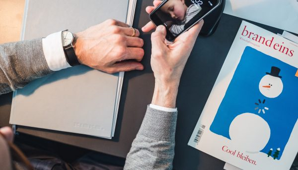 Brand consultant looking at smartphone with notebook in KISKA brand corporate design