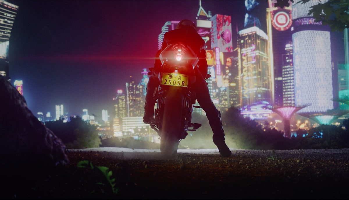 Rear view of the CFMOTO 250SR and rider looking at a city at night